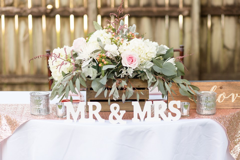 mr and mrs table sign with white flowers and greenery