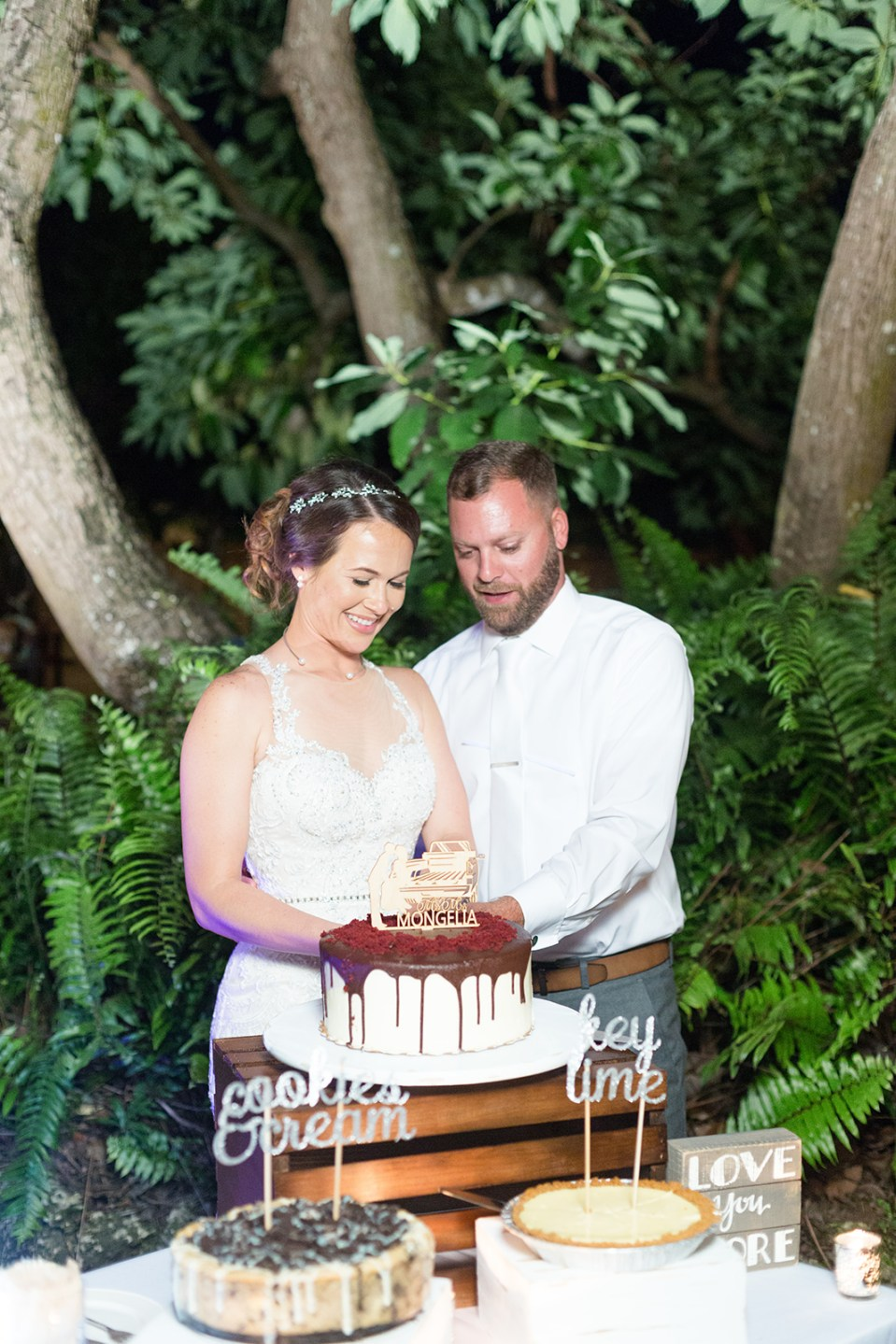 bride and groom cutting delicious wedding cake