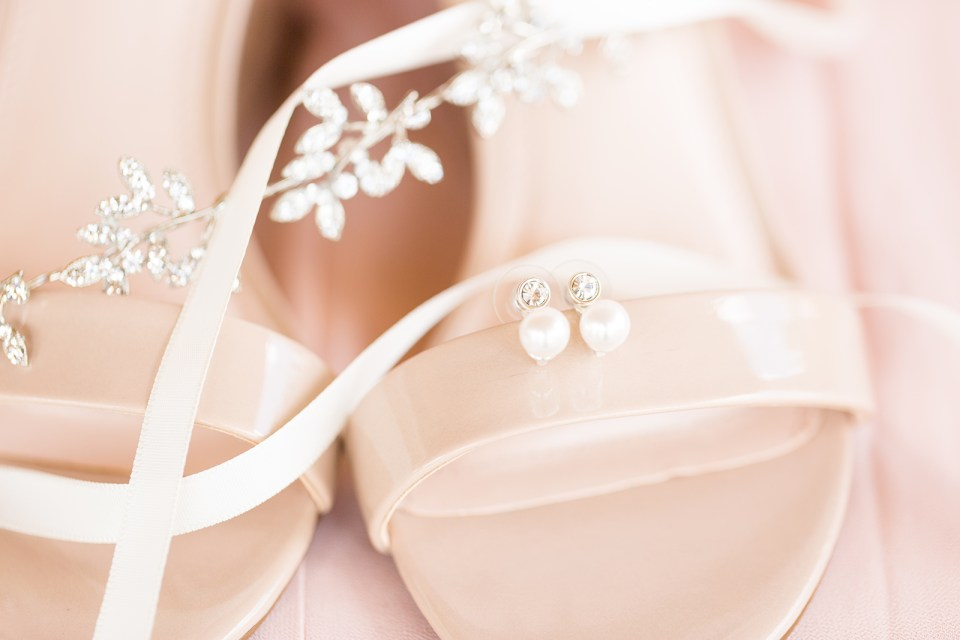 brides beige shoes with pearl earrings and ribbon on top