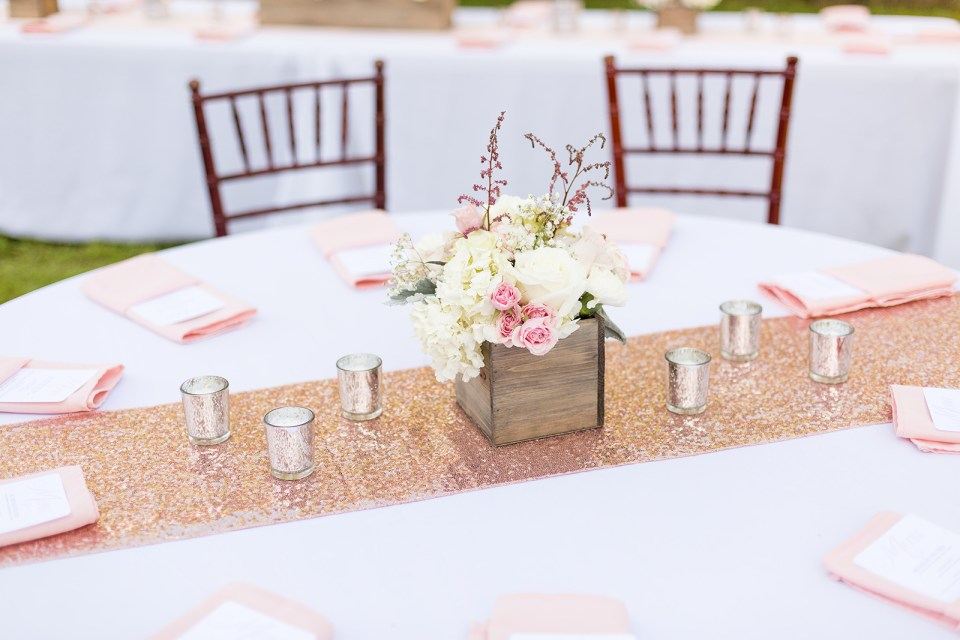 table with light colored pink and white flowers and pink napkins in a Miami backyard wedding