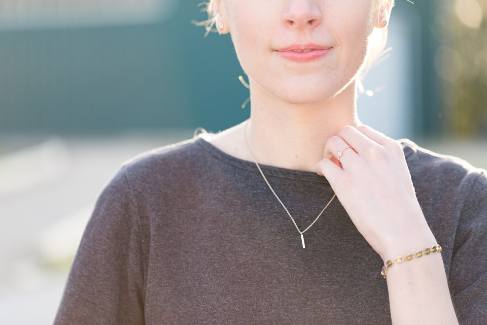 closeup of woman from nose to chest in a grey sweater and dainty gold necklace