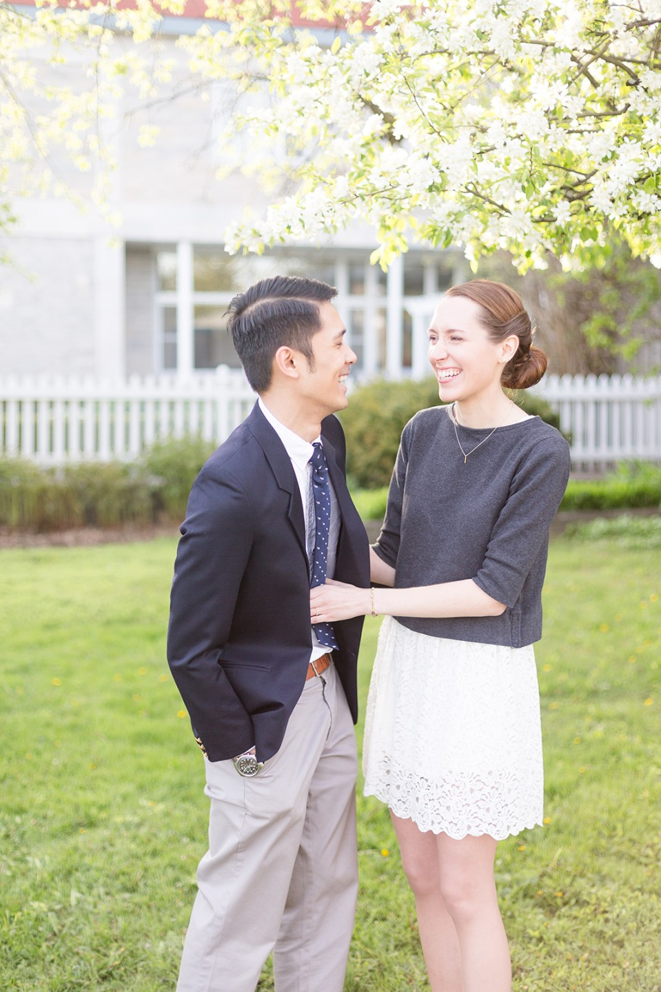 standing couple laughing while taking their Fergus Ontario engagement photos at the Wellington County Museum