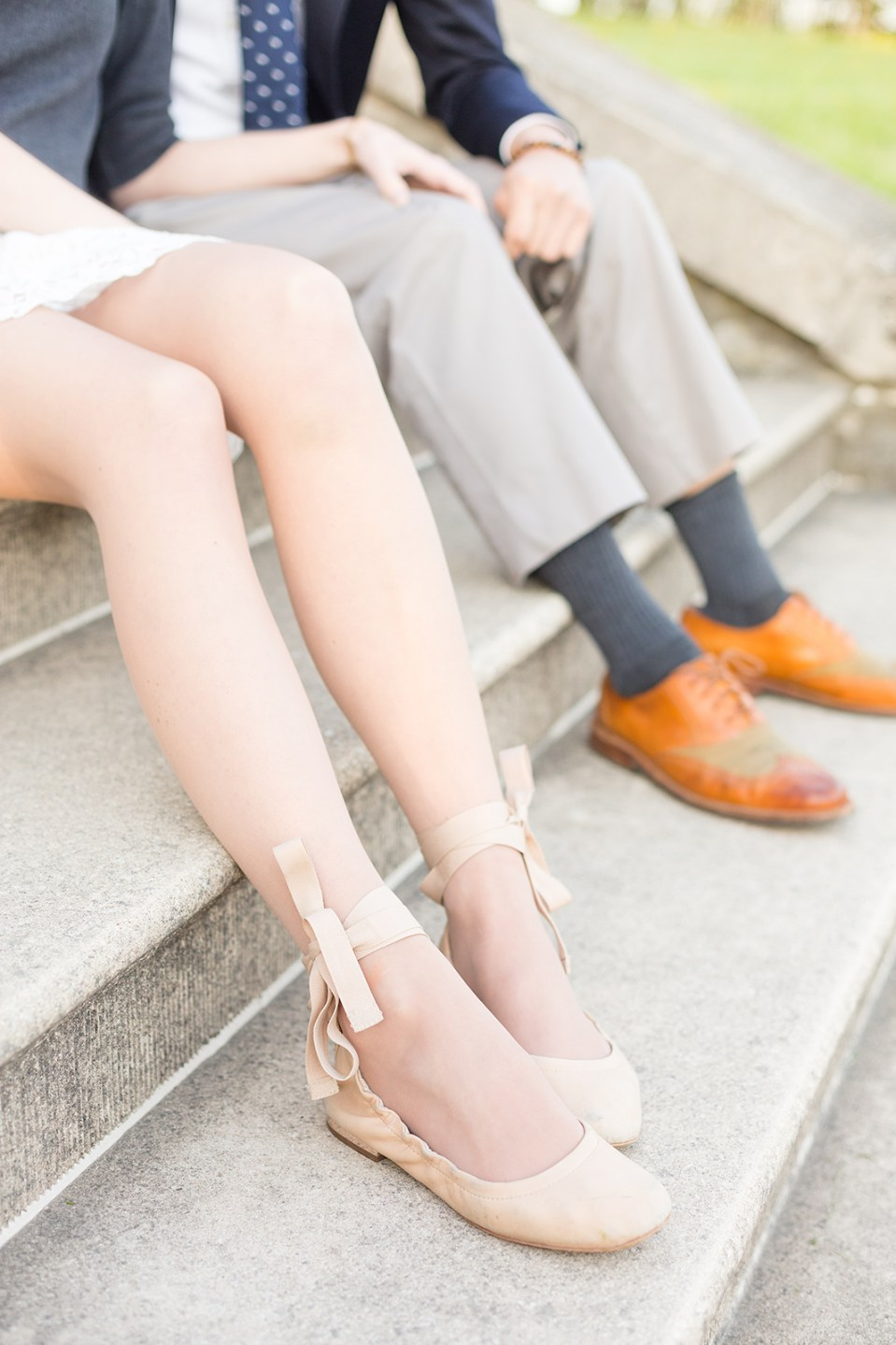 closeup of woman and man's legs sitting on stairs with nude and brown shoes