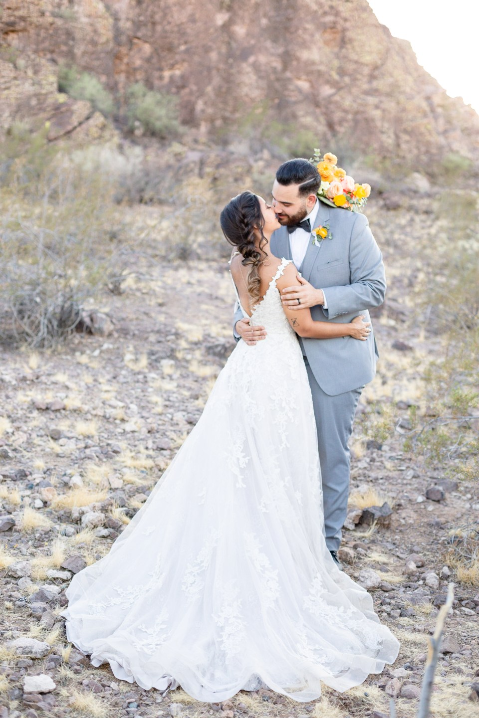 Bride and groom kissing with orange and yellow flowers on Arizona mountain