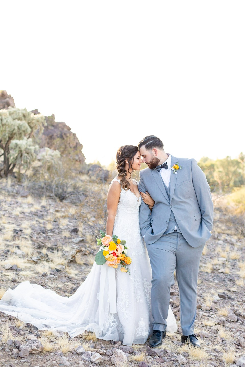 Bride and groom standing nose to nose with orange and yellow flowers on Arizona mountain
