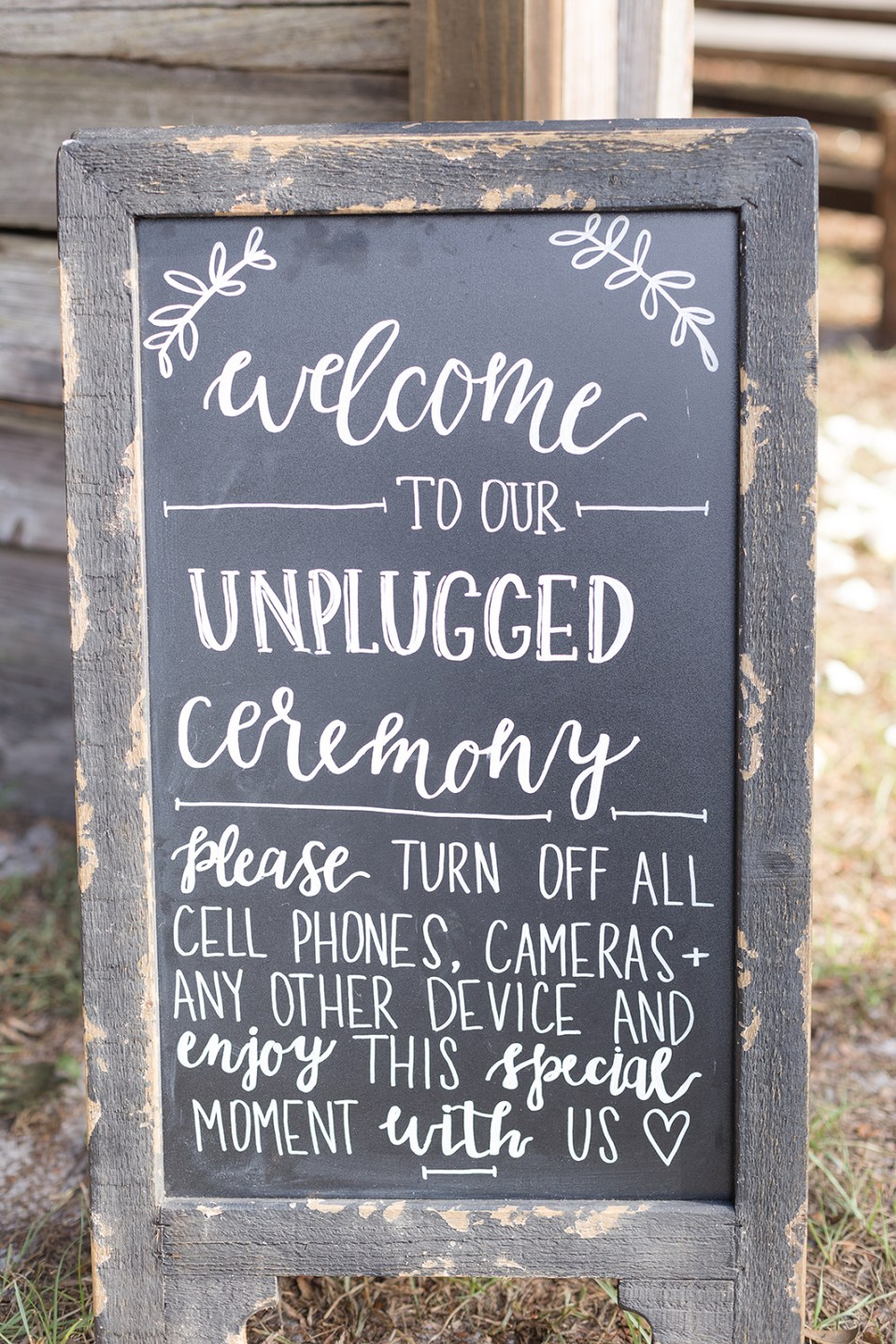 Chalkboard sign that says Welcome to our unplugged wedding ceremony