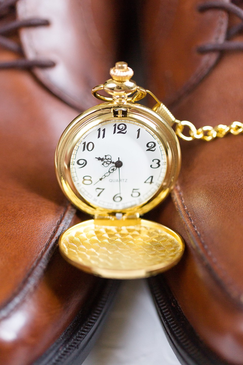Gold pocket watch on brown dress shoes