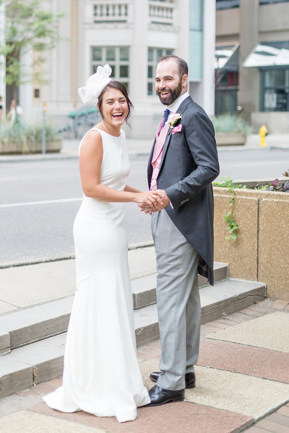 bride and groom laughing in front of the Royal Canadian Military Institute