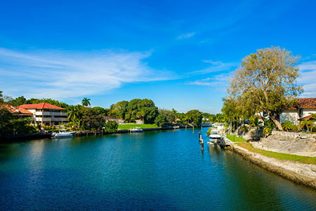 Coral Gables waterfront homes and boats along a waterway in miami, florida.