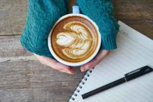 Hands holding coffee next to a pen and notebook