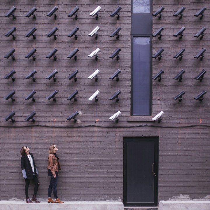 Many cameras on a wall facing two women
