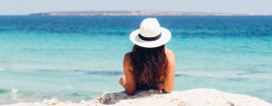 Woman in a white hat, sitting on the beach, looking out at the ocean