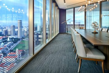 Interior Photography of the Sky Premium boardroom in Singapore showing the backs of chairs and the skyline view of singapore