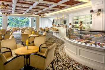 Interior photography of the tea room restaurant showing countertop with staff and seating at tanglin club in singapore