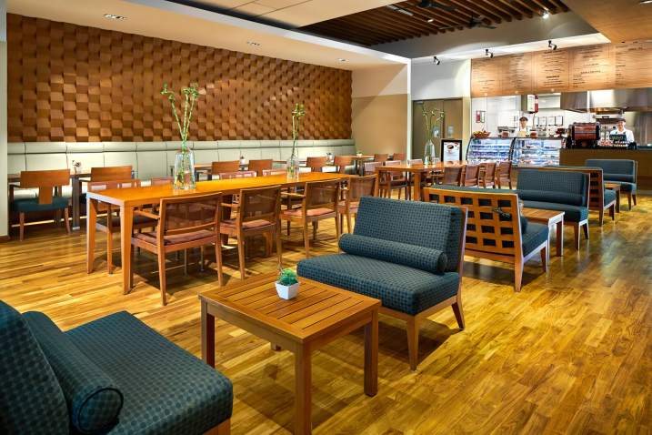 interior photography showing tangles restaurant with eating area and counter with staff at tanglin club in singapore