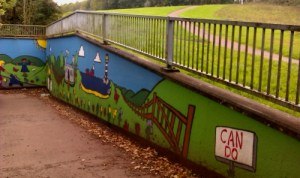 A bright mural on the walls of a concrete underpass