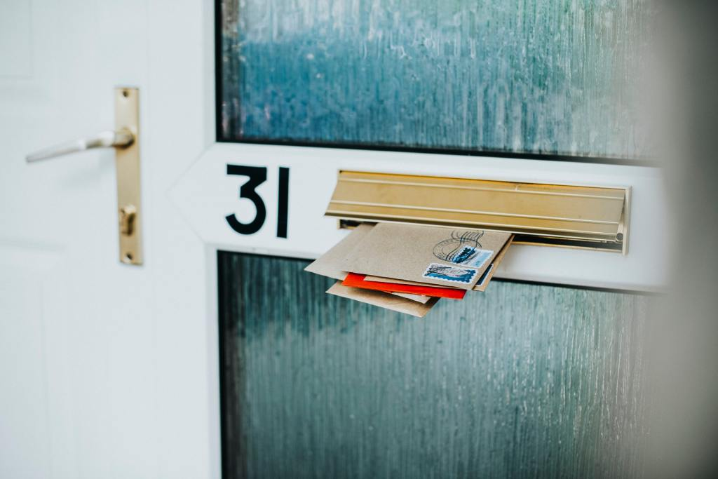 Letters delivered through door mail slot.
