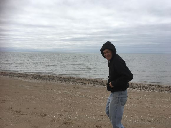 Image of Chris walking along the edge Lake Ontario at Southwick State Park beach.