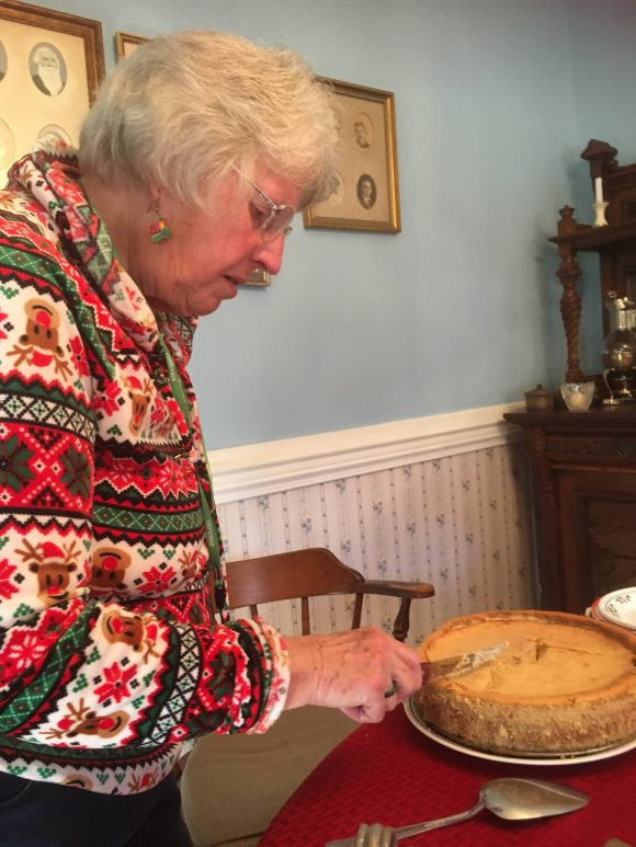 Aunt Anne cutting the pumpkin cheesecake.