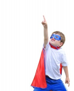 Boy dressed as superheo pointng up