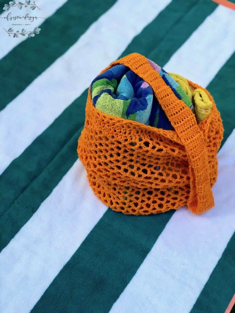 picture of orange crochet market tote bag on striped towel