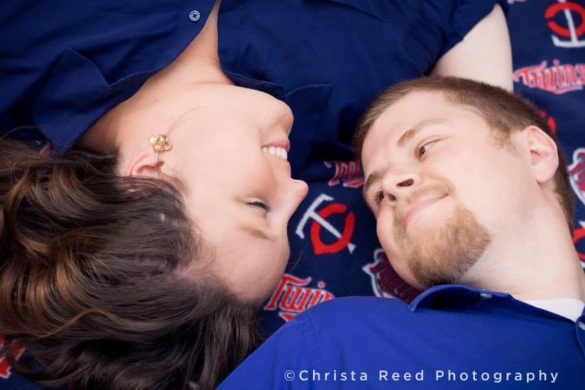 a couple lays on a Minnesota Twins blanket for their engagement portraits