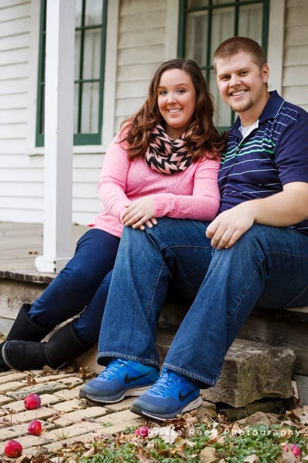 a couple sits on on the steps of a historic house for their engagement photos in belle plaine