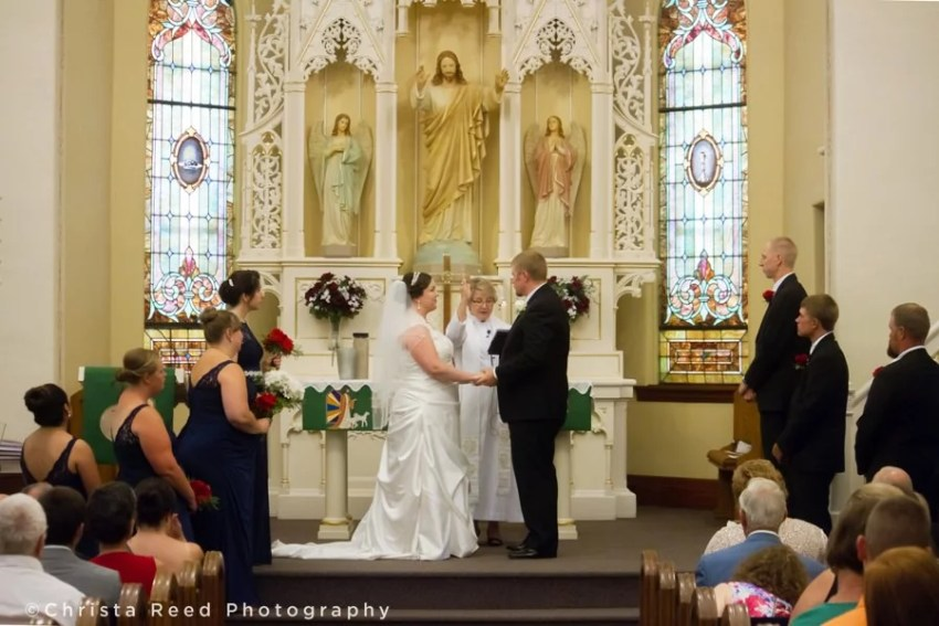 blessing the couple at the altar in st john lutheran church