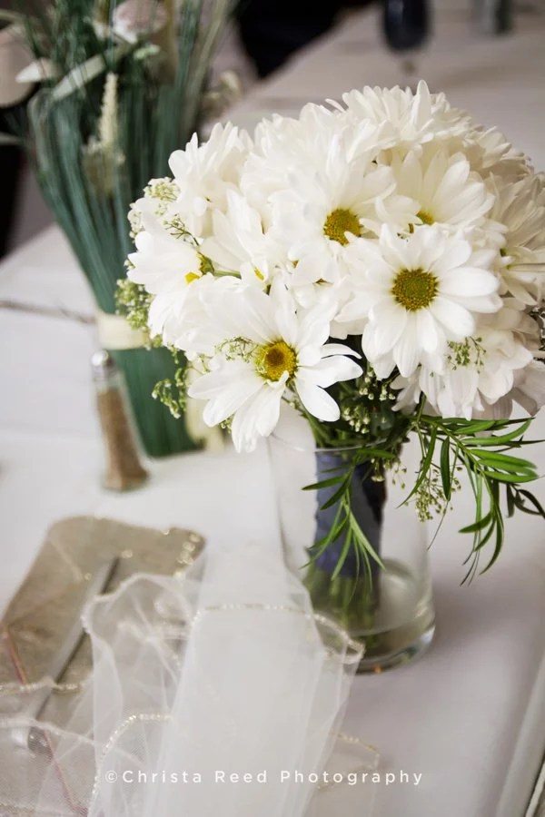 daisy bridal bouquet on the table at wedding reception