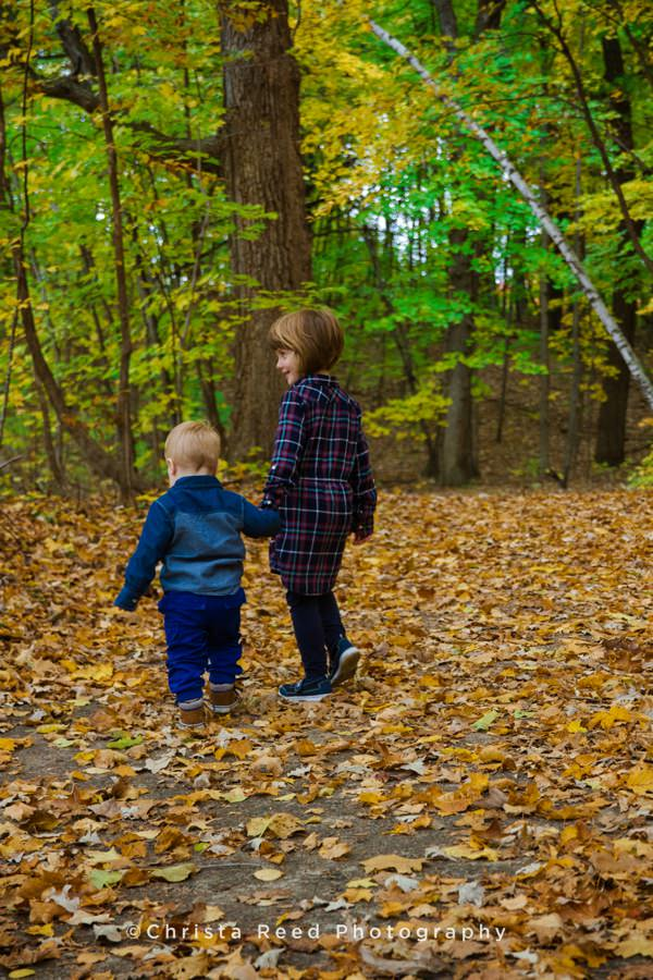 kids hold hands in the woods with orange fall leaves