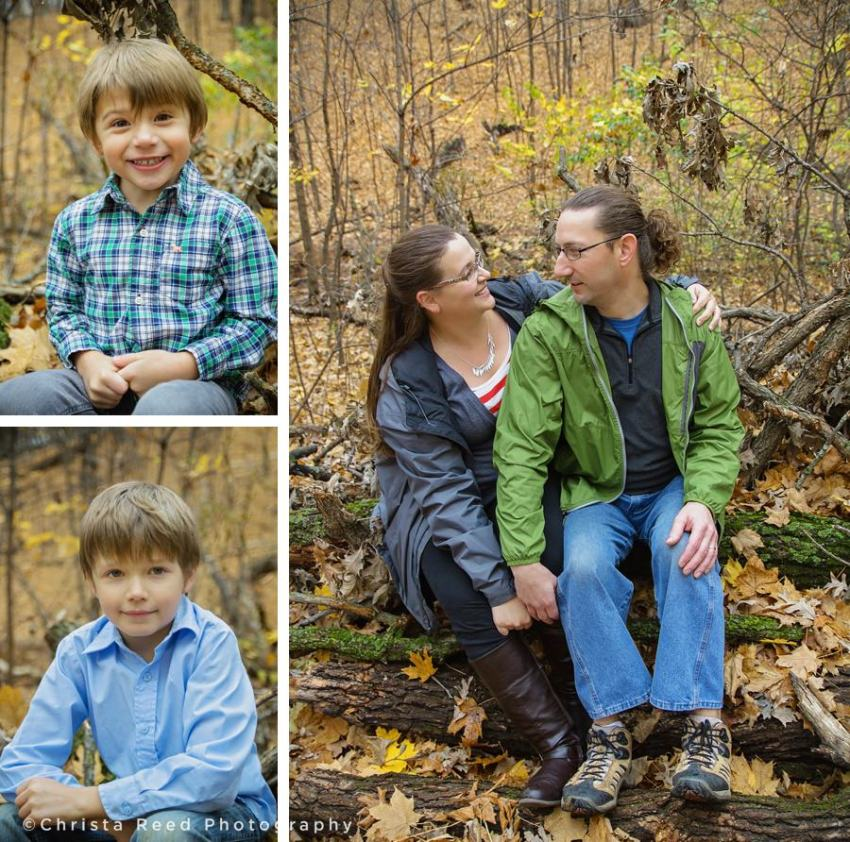family sits on log in the woods for portraits at lake ann park