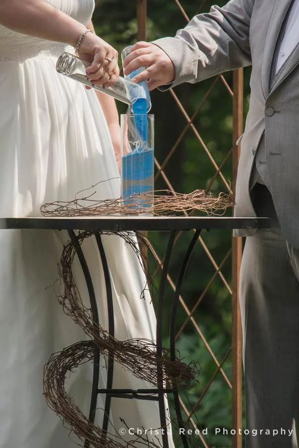 pouring sand into vase for wedding