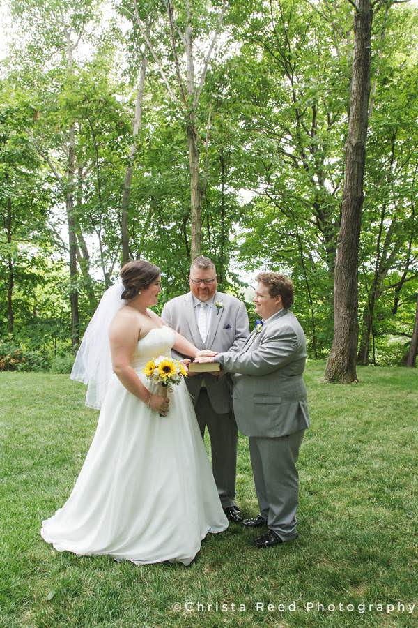 officiant with bride groom and bible after ceremony