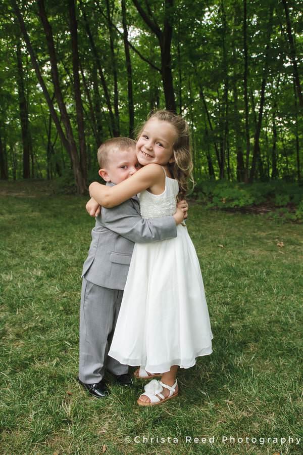 adorable flower girl hugs ring bearer