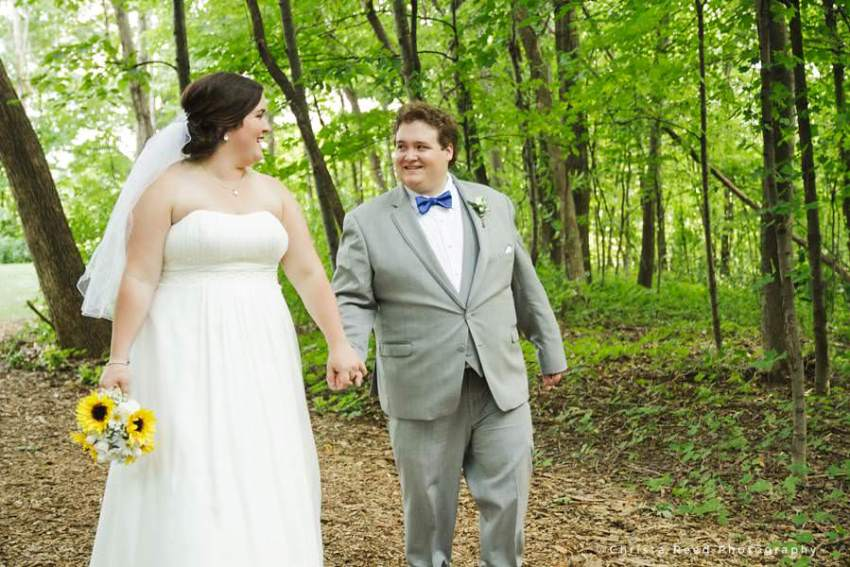 bride and groom walk in the woods holding hands