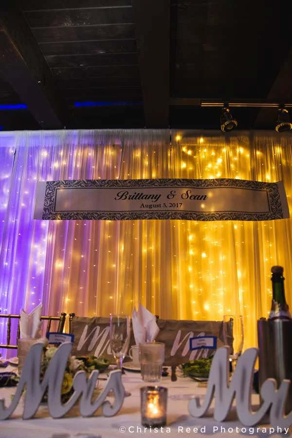 colorful lights behind table at wedding reception