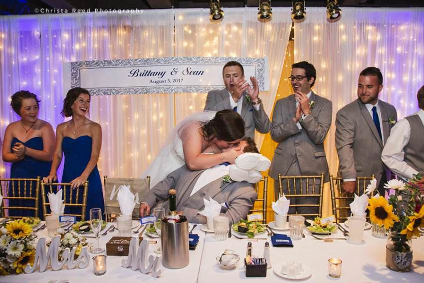couple kisses during wedding reception at chanhassen dinner theatre