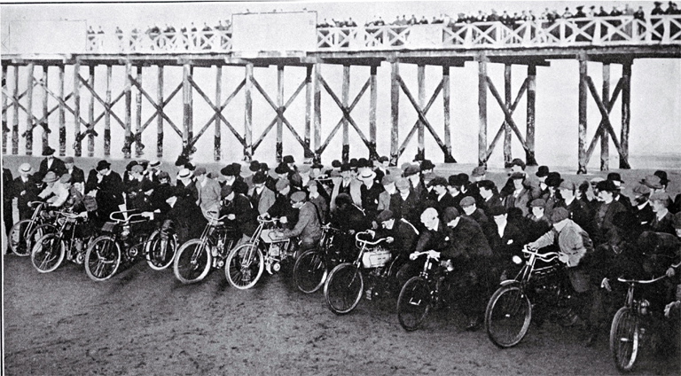 The Christchurch Motor and Cycling Club's motor races on New Brighton Beach, Christchurch  [1905]  The start for the scratch race of nine miles is shown. B. Ogilvie was the winner. The original New Brighton Pier, which was in existence 1894-1965, is shown
