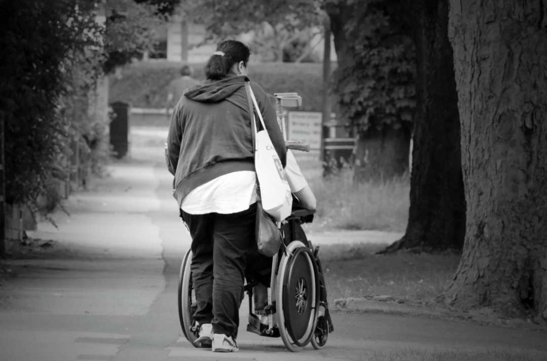 Woman pushing someone in a wheelchair