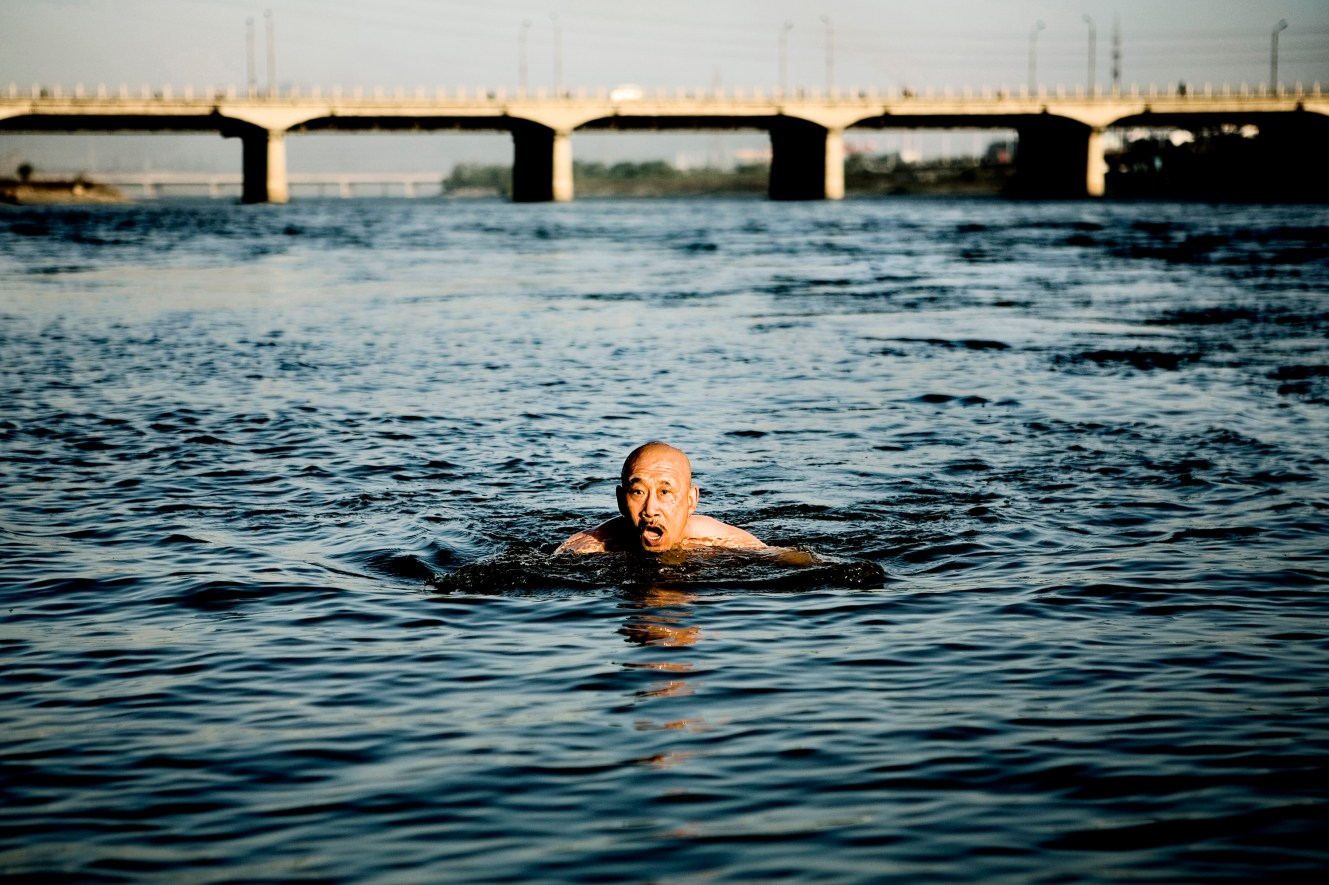 A member of Jilin Swimmers Club is taking the yearÕs first dive in the icy Songhua River. The club has more than 500 members and they meet every morning from May to September to swim in the river. Christian Als / GraziaNeri