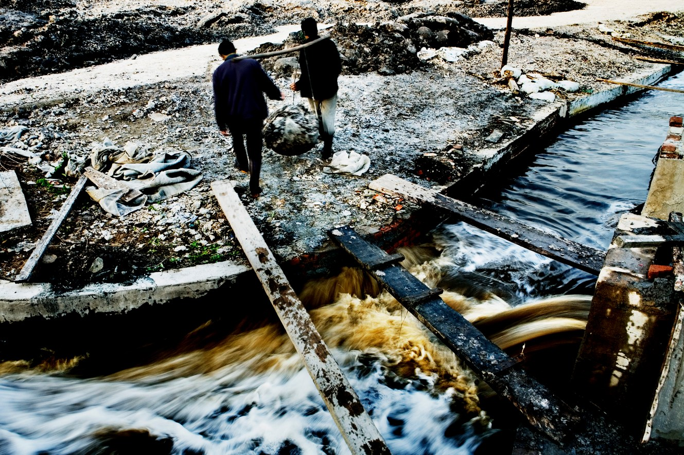 The two brothers Jiang Ji Quan and Jiang Jichao are working at the site of the wastewater run-out from a polluting paper factory in Jilin. They filter the dirty wastewater and recycle the bits of paper that they carry away, later to be loaded on a truck. Christian Als / GraziaNeri