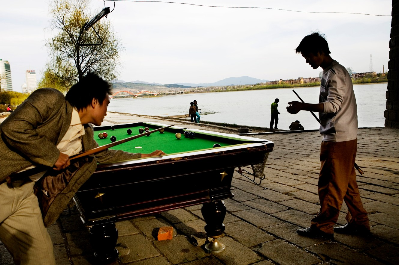 Two teenagers play a round of pool in the shadow of Jilin Bridge. The Songhua River front is the popular scene of kissing couples, karaoke singers, boat renters and fishing men. Christian Als / GraziaNeri