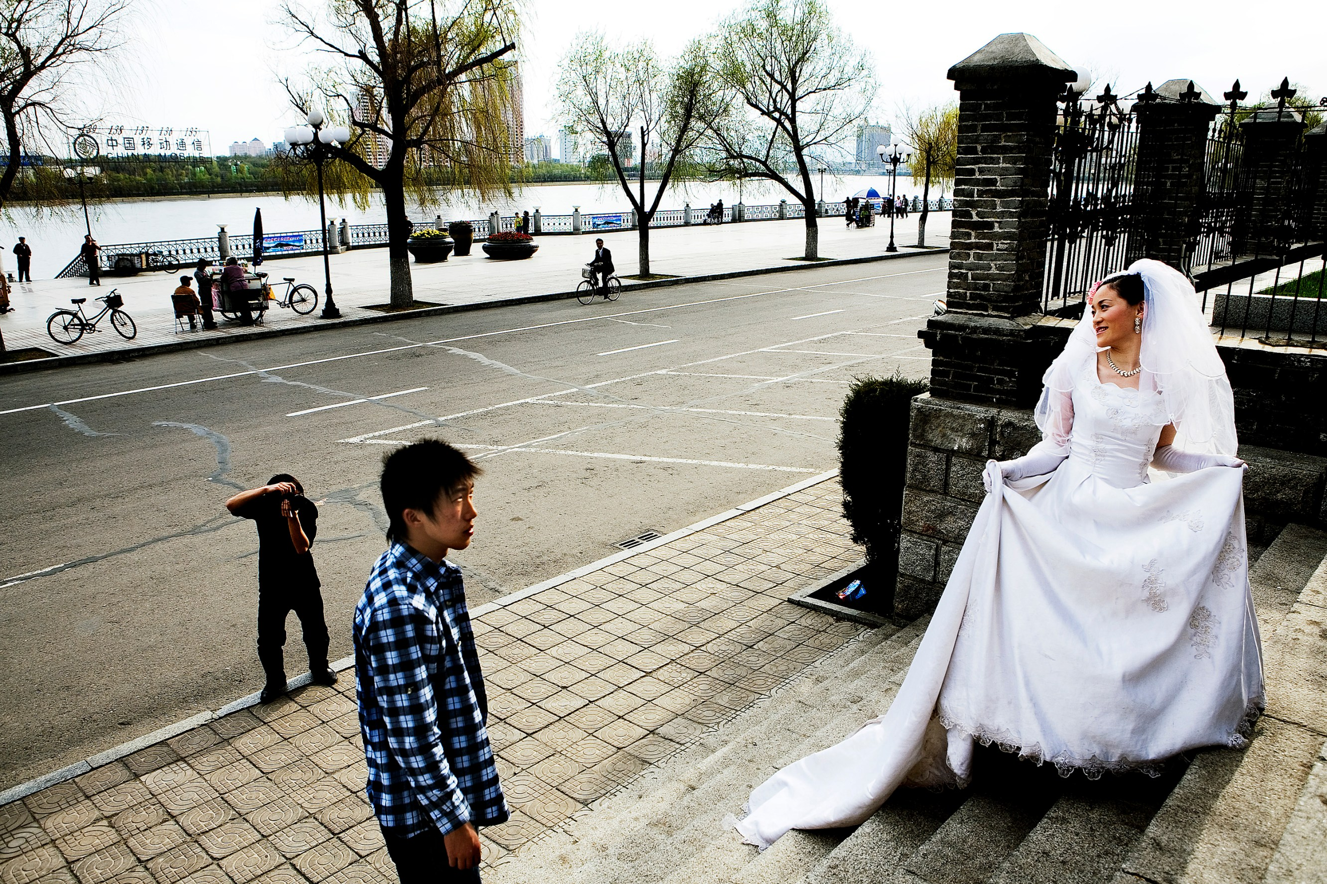 A newlywed bride poses for the standard wedding photos in front of a church on the Songhua River in Jilin. Christian Als / GraziaNeri