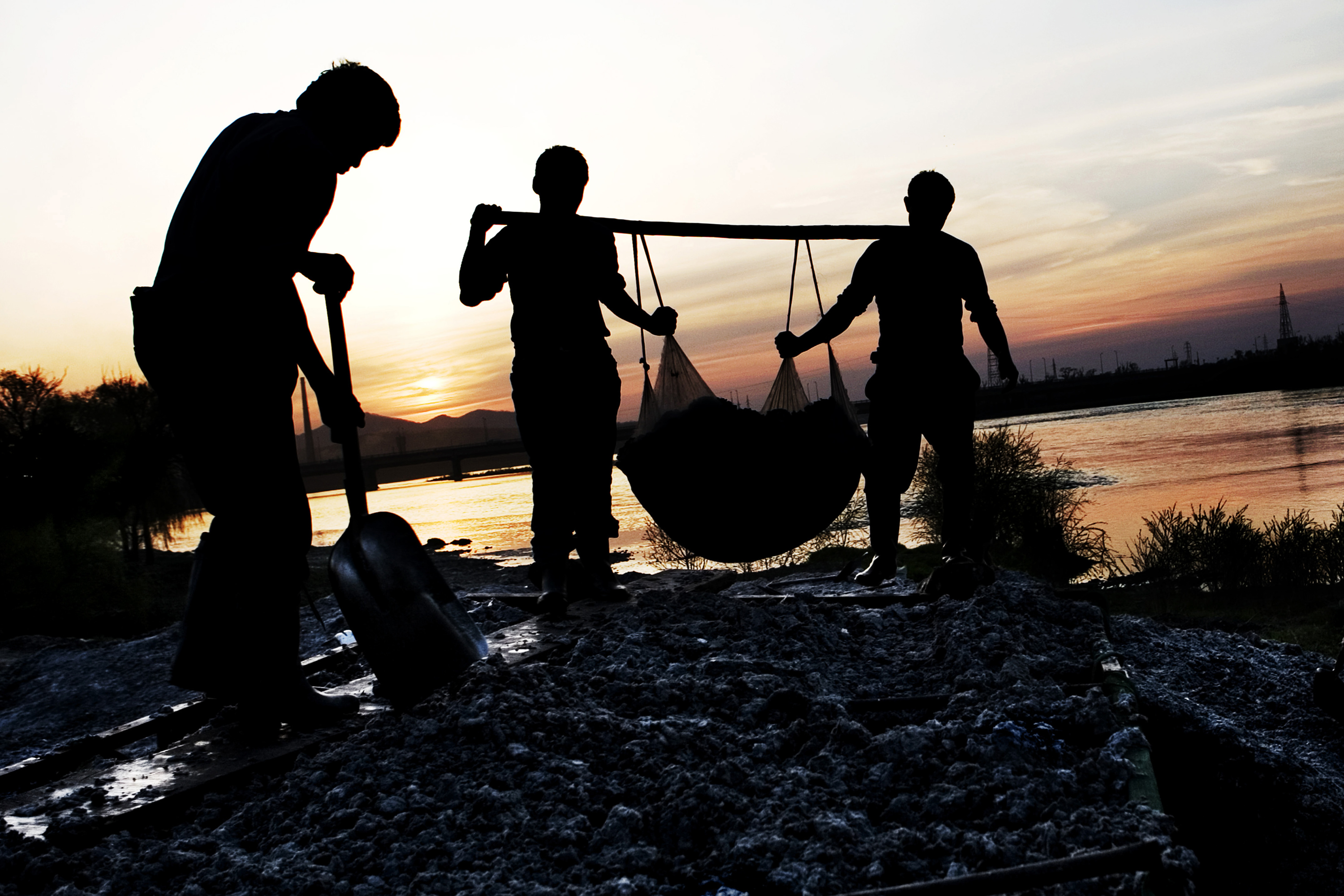 As dusk settles on the Songhua River two brothers of the migrant family carries yet another load of paper bits onto the truck. Each worker gets approximately 3 dollars for a truckload. Christian Als / GraziaNeri