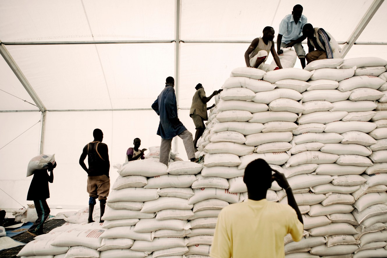 Men stack sacks of lentils in a World Food Programme (WFP) food distribution point in the Jammam refugee camp.