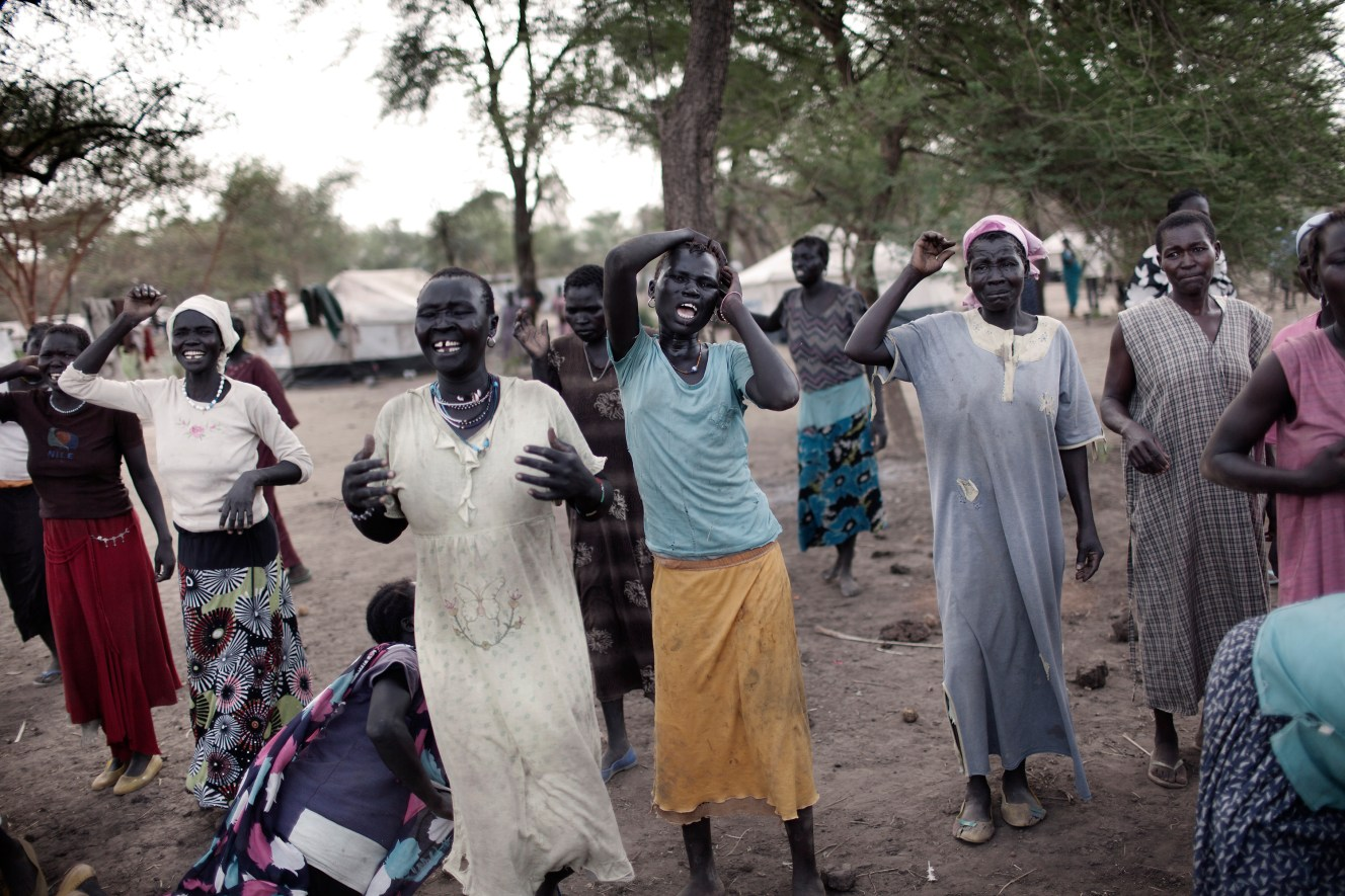 Relatives and friends of a man stabbed to death with a spear, mourn as they stand beside his bloodied corpse in Doro refugee camp. The death was the result of an inter-tribal conflict, one of many assaults and murders occuring in the refugee camps of South Sudan.