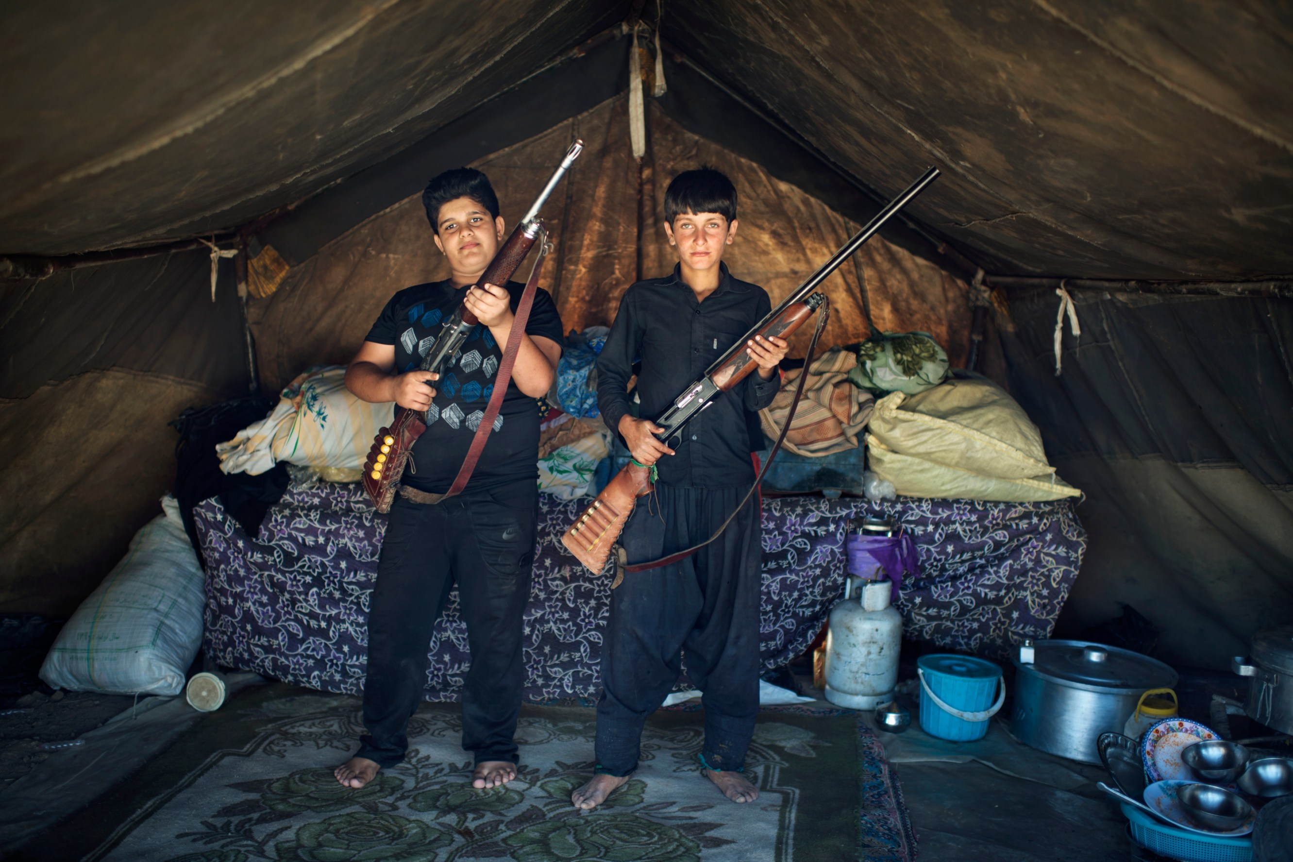 Two boys, belonging to the Lor tribe, pauses with riffles in a tent in Bazoft Valley.