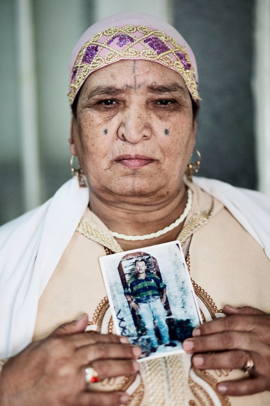 Safia Azeb holding a picture of her missing son Feghoul, who disappeared in 1996.