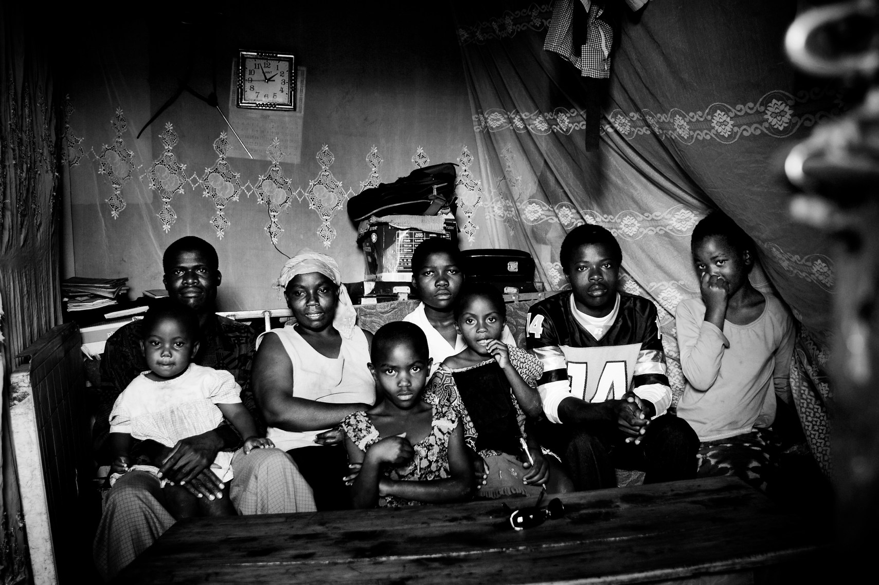 The Odongo Family in the stick and mud house. From left to right it is Augustin Odongo with Michelle, Clarissa Adiambo, Cynthia, Lavenda, Naomi, Meshak and Eunice.