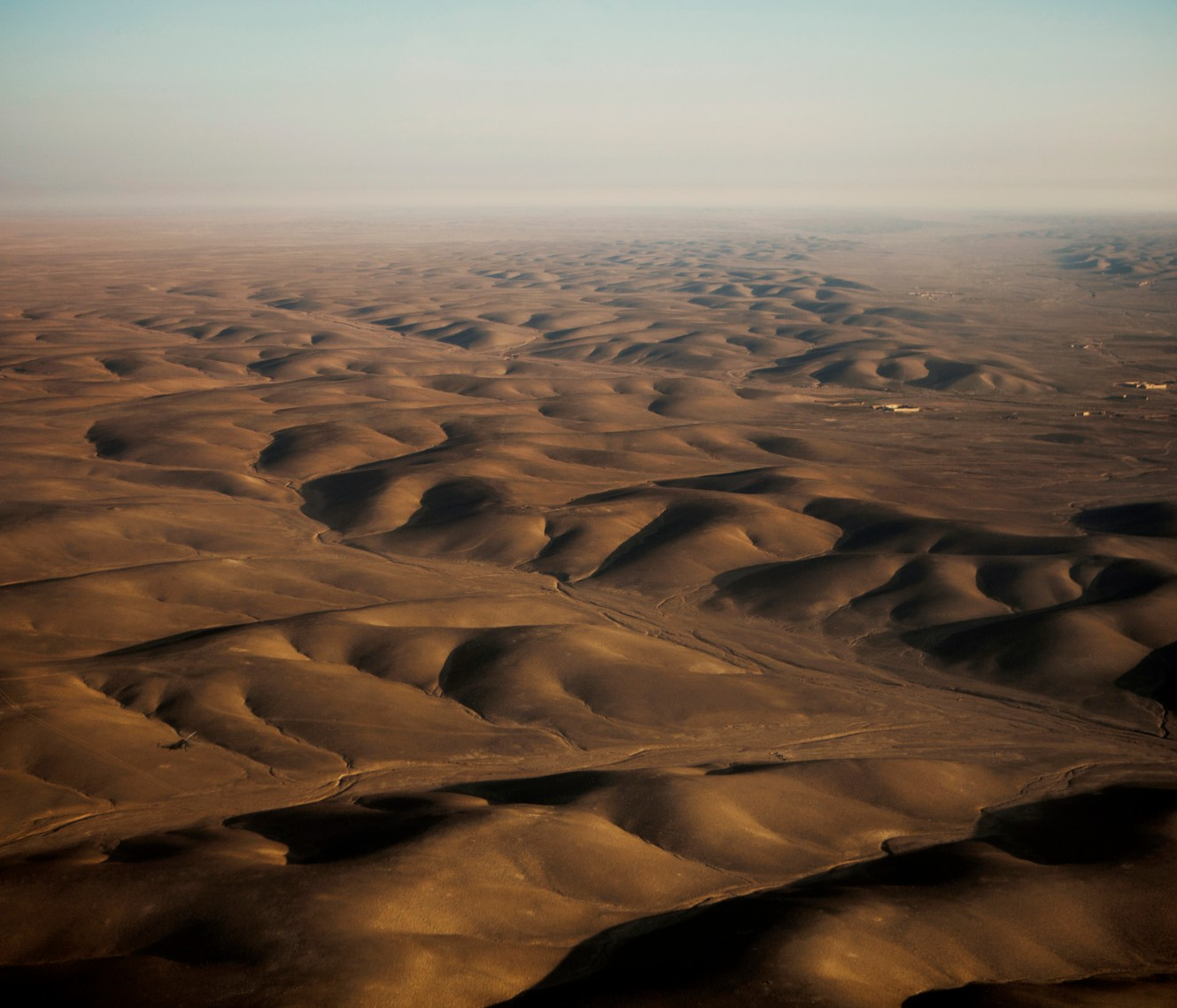 An aerial view of the dry, low hills near Camp Bastion. In June 2011, President Obama announced his plan to begin the withdrawal of US troops from Afghanistan, but there is currently no end date for the war in the troubled country. Helmand is the largest province in Afghanistan, and the heart of the war against terror. Commanders on the ground have described the situation as the most brutal conflict the British Army has been involved in since the Korean War. Much of the fighting between NATO and Taliban forces is taking place in this province and Helmand is a true Taliban stronghold. The Helmand River flows through the mainly desert region. With these images I am trying to show a softer side to this troubled area of Afghanistan.